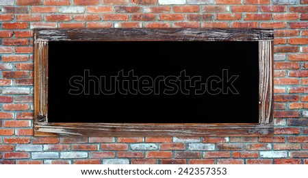 Empty vintage chalk board on brick wall background, wording template - stock photo