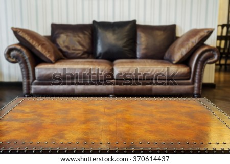 Empty vintage wooden table and blurred luxury leather sofa background - stock photo