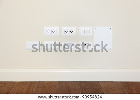 Empty wall with wooden floor. On the wall power outlet and  light switch - stock photo