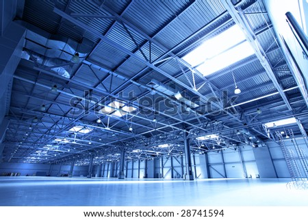 Empty warehouse toned in the blue color - stock photo