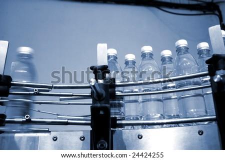 empty water bottles on factory conveyor belt - stock photo