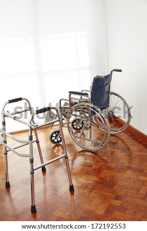 Empty wheelchair and wallker in nursing home as symbol for death - stock photo