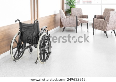 Empty wheelchair parked in hospital hallway - stock photo