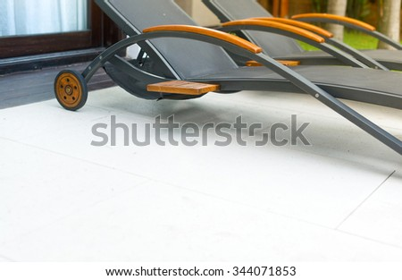 Empty wheeled chaise longues on tiled floor outdoor in hotel area.  Relaxation and sunbathing on hot day. Summer holidays and vacations in tropical countries. Hotels and resorts. - stock photo
