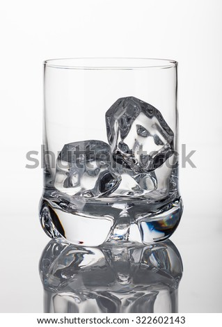 Empty whisky glass on white background with reflection - stock photo