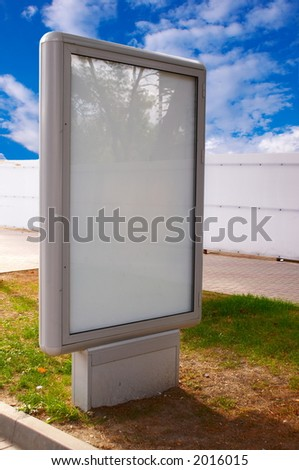 Empty white advertisement hoarding on a lawn - stock photo