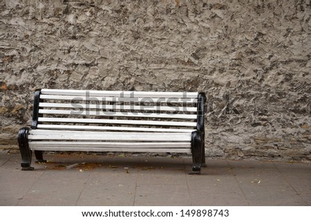 Empty white bench in front of wall - stock photo
