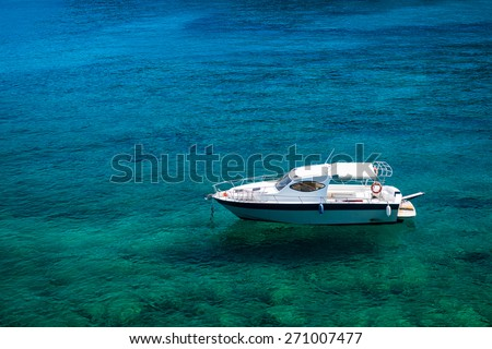 Empty white boat floating on clear turquoise water - stock photo