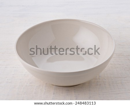 Empty white bowl on wooden table - stock photo