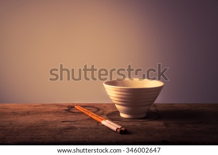 Empty white bowl with chopsticks on wooden table - stock photo