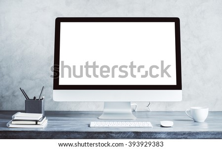 Empty white computer screen on wooden desktop with coffee cup and other items. Mock up - stock photo