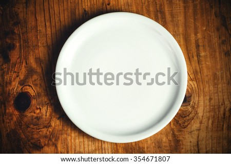 Empty white dinner plate on rustic wooden kitchen table, top view - stock photo