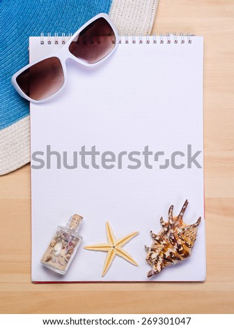 empty white notebook on wooden table surface with beach hat, seashells, starfish, sunglasses - stock photo