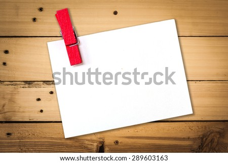 empty white paper with wood clip on wooden background  for text. - stock photo