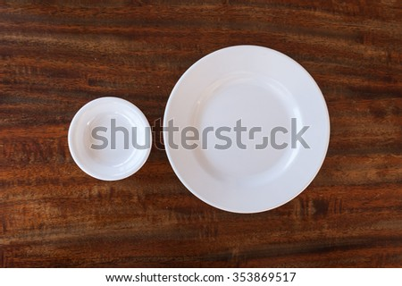 Empty white plate and small chalice on wooden background - stock photo