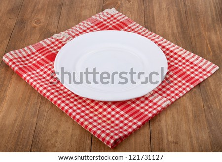 Empty white plate at classic checkered tablecloth on wooden table - stock photo