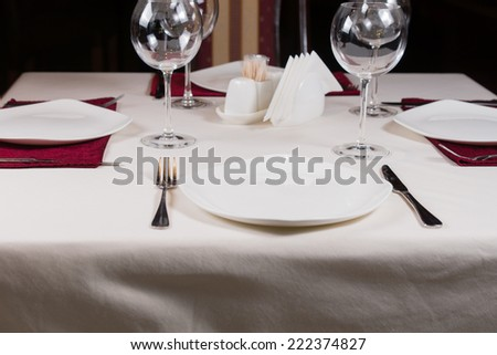 Empty white plate in a formal table setting on a table set with a white tablecloth, wineglasses and cutlery - stock photo