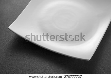 Empty white plate on black textured background - stock photo