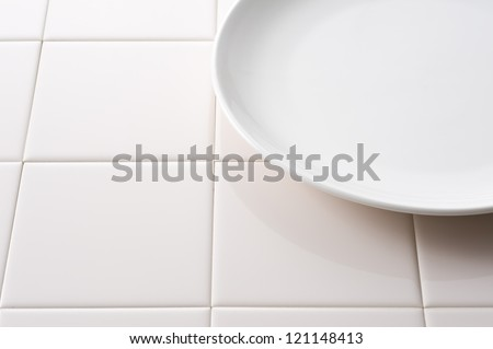 Empty white plate on tile background, close-up - stock photo