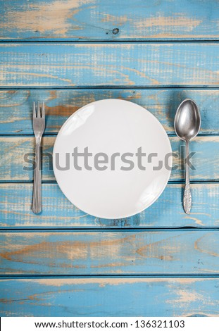 Empty white plate on weathered blue wooden table - stock photo