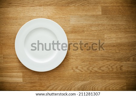 Empty white plate on wooden table. Template for your design. - stock photo