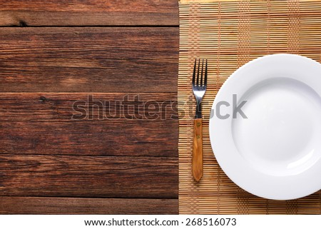 empty white plate with old fork on rustic wooden background  - stock photo