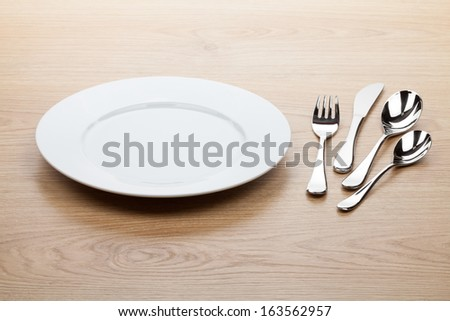 Empty white plate with silverware on wooden table - stock photo