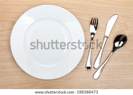 Empty white plate with silverware on wooden table. View from above - stock photo