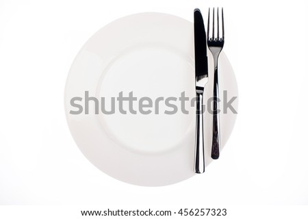 Empty white plate with the knife and fork on white background - stock photo