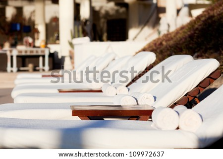 empty white sunbeds by the resort pool - stock photo