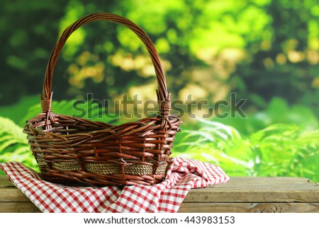 empty wicker basket and checkered plaid for picnic  - stock photo