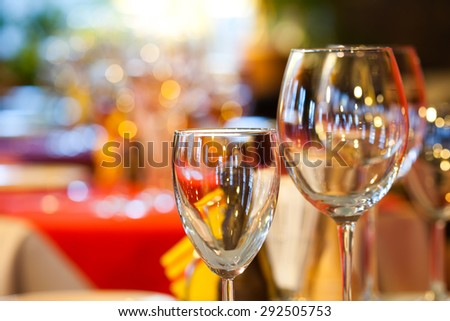 Empty wine glasses, closeup. Bright blurred and soft restaurant, cafe interior background. evening time. soft focus, copy space - stock photo