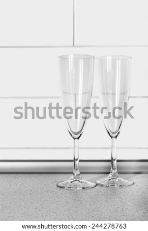 Empty wineglasses on a table against  brick wall as a background - stock photo