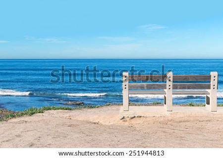 Empty wood bench on cliff top overlooking the ocean. Rolling waves. Blue sky, horizon view. Room for text, copy space.  - stock photo