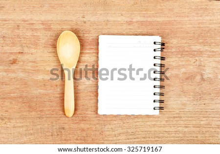 empty wood plate with notebook open and spoon  - stock photo