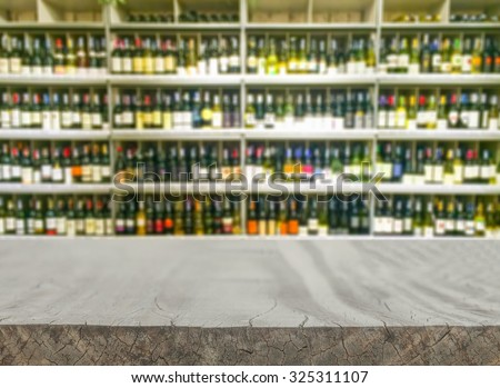 Empty wood table top (or shelf) shelf with wine liquor bottle in supermarket blurred background - can montage or display your products - stock photo