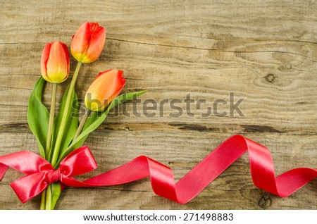 Empty wooden background with colorful flowers and red ribbon - stock photo