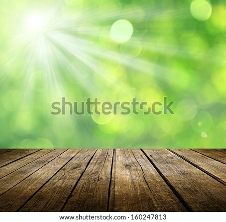 Empty wooden deck table with green background. Ready for product display montage. - stock photo
