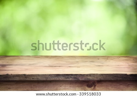Empty wooden deck table with green soft focus background. Ready for product display montage. - stock photo