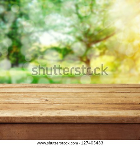 Empty wooden deck table with park bokeh background. - stock photo
