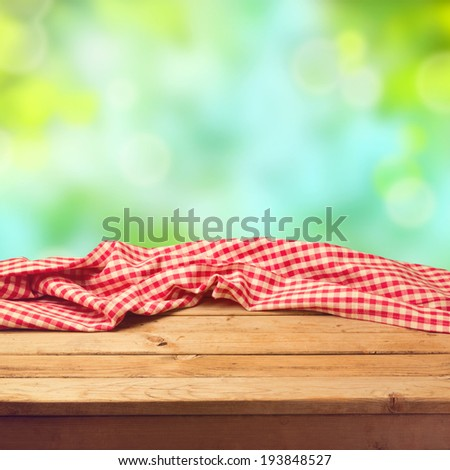 Empty wooden deck table with tablecloth over nature background - stock photo