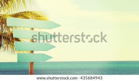 Empty wooden direction sign at the tranquil beach - stock photo