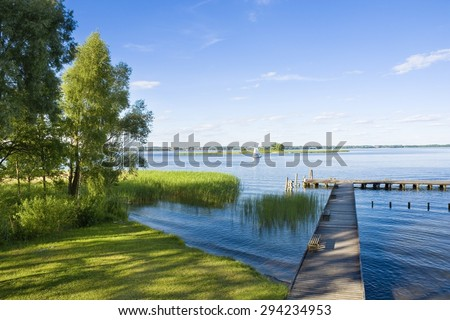 Empty wooden jetty on the lake shore with island and yachts in the background - stock photo