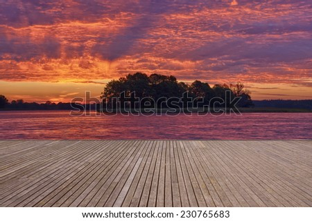 Empty wooden jetty on the lake shore with small island and clouds floodlit by rising sun in the background - stock photo