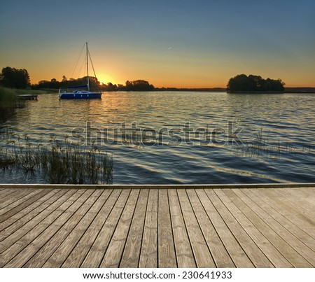 Empty wooden jetty on the lake shore with small island and sailboat in the background just before sunrise - stock photo
