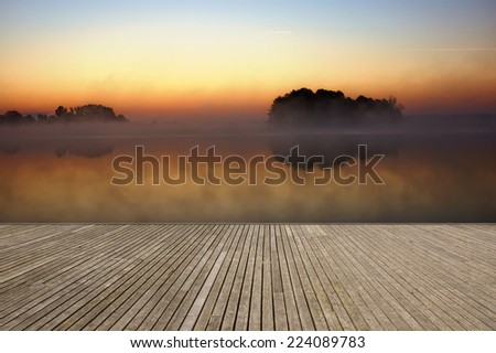 Empty wooden jetty on the lake shore with small island on calm foggy lake water surface just before sunrise in the background - stock photo