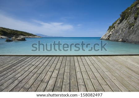Empty wooden jetty on the seashore with idyllic view in the background - stock photo
