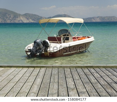 Empty wooden jetty on the seashore with motorboat in the background - stock photo