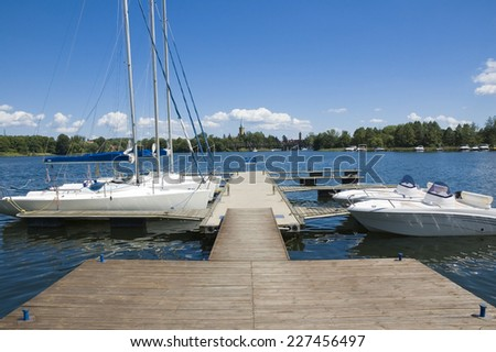 Empty wooden jetty with moored boats on the lake shore - stock photo