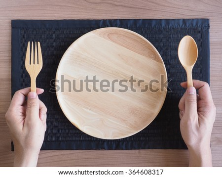Empty wooden plate with wooden spoons and forks in the hands on woven placemat - stock photo